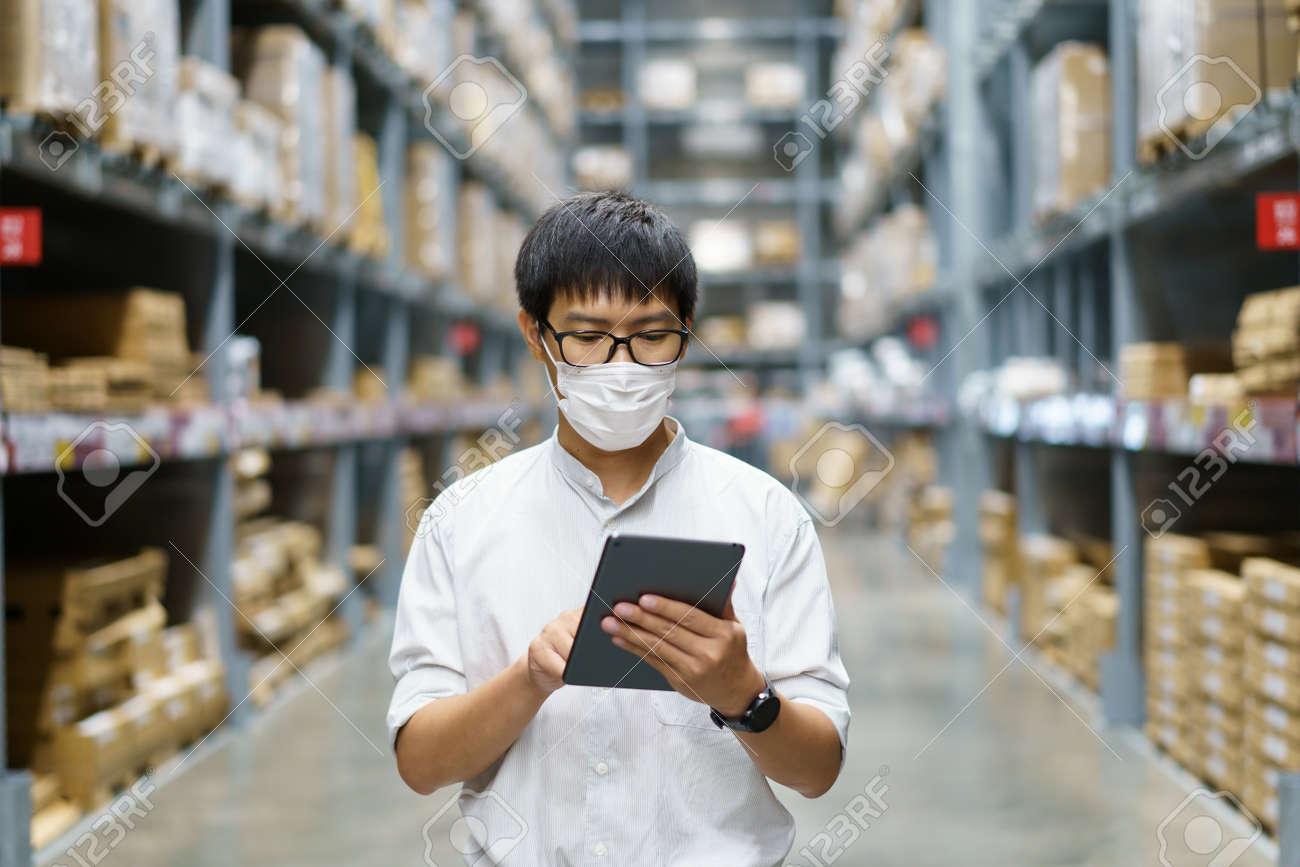 Portrait Asian men, staff, product counting Warehouse Control Manager Standing, counting and inspecting products in the warehouse - 171394282