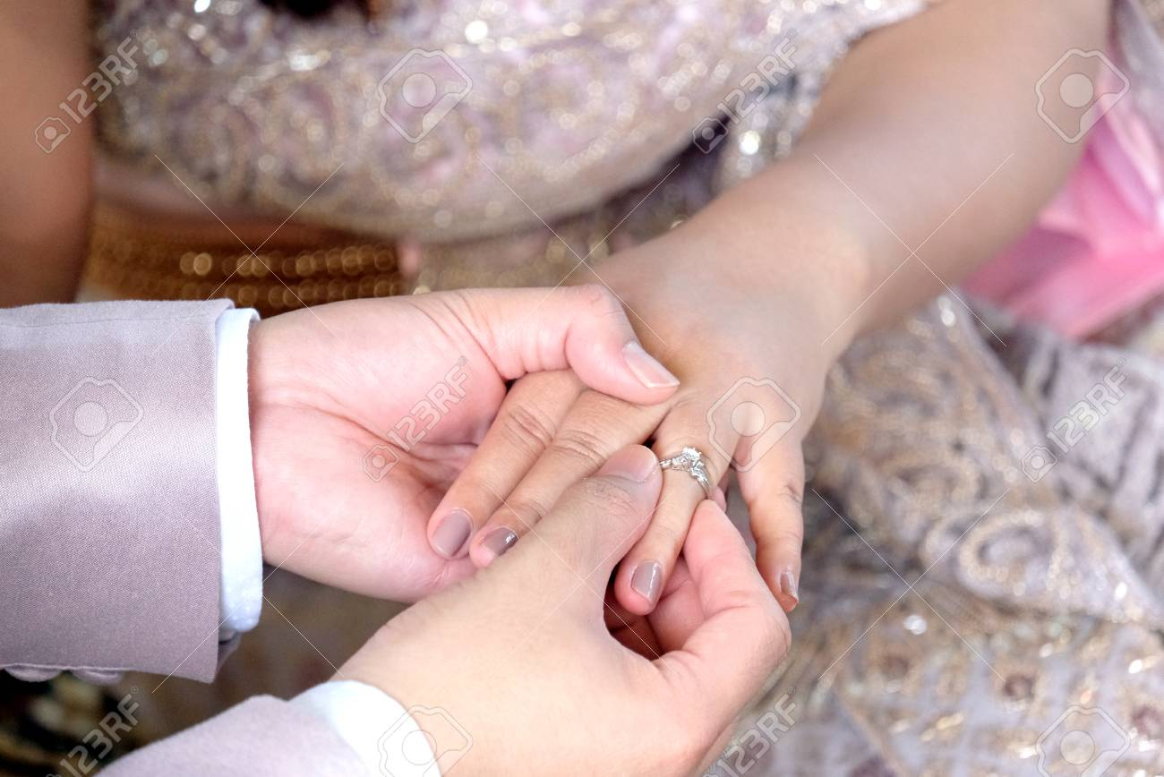 Thai Wedding Groom\'s Hand Putting A Wedding Ring On The Bride\'s ...