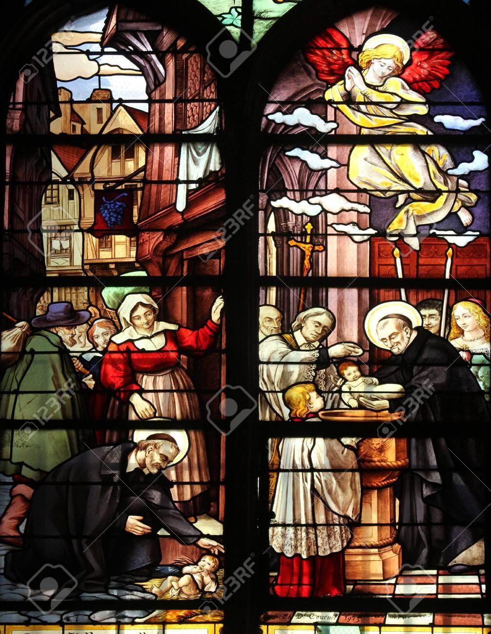 Saint Vincent de Paul raising a newborn and christening, stained glass, Saint Severin church, Paris, France Stock Photo - 21106542