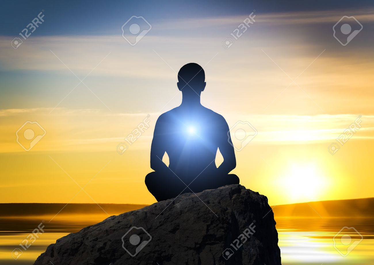 Silhouette of the meditating person against a fired background Stock Photo - 12778756