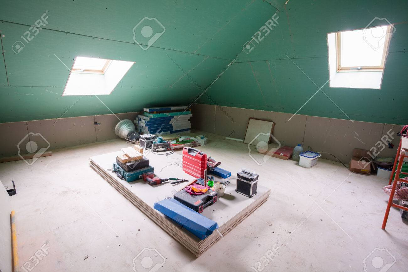 Sheets of drywall, parts of scaffolding, handle tools and construction material in the room of apartment during on the remodeling, renovation and construction - 75398230