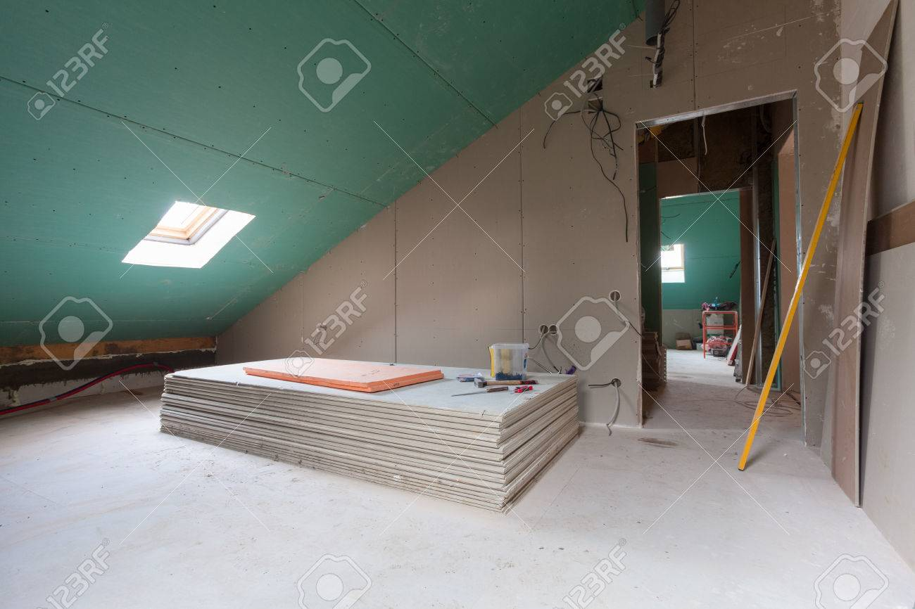 Sheets of drywall, parts of scaffolding, handle tools and construction material in the room of apartment during on the remodeling, renovation and construction - 75393342