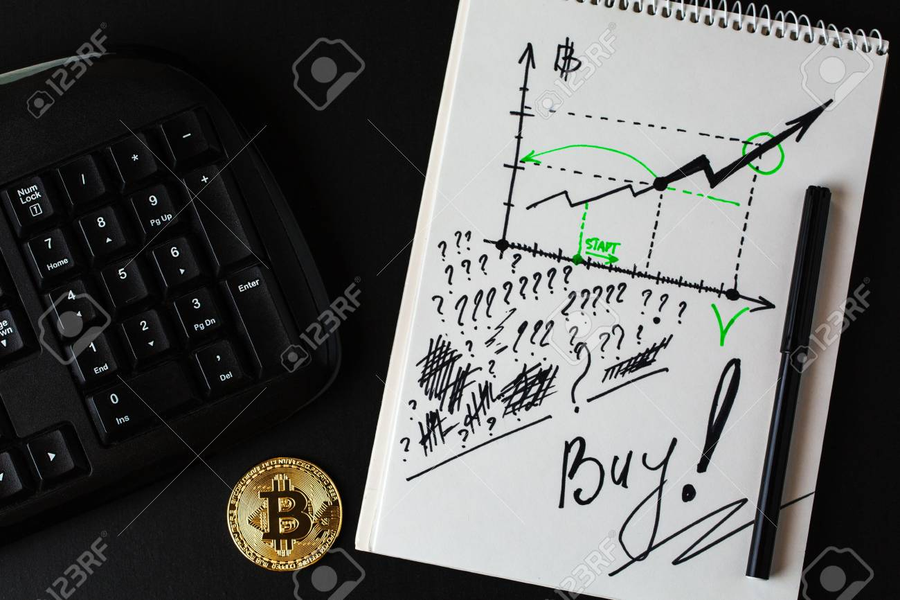 Gold bitcoin, part of keyboard and ring-bound notebook with