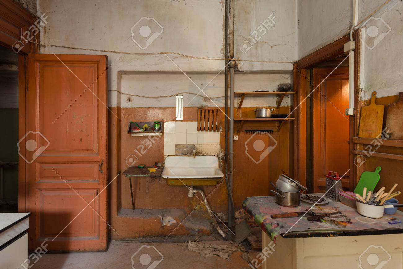 Dirty kitchen with furniture and gas stoves is in the apartment..