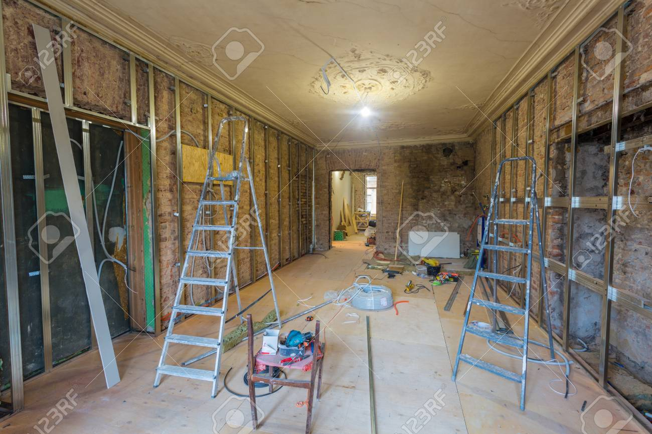 Working process of installing metal frames for plasterboard (drywall) for making gypsum walls with ladders and tools in apartment is under construction, remodeling, renovation, extension, restoration and reconstruction - 95391866