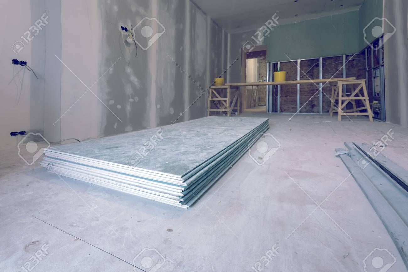 Working process of installing metal frames and plasterboard (drywall) for gypsum walls and materials are in apartment is under construction, remodeling, renovation, extension, restoration and reconstruction - 96444326