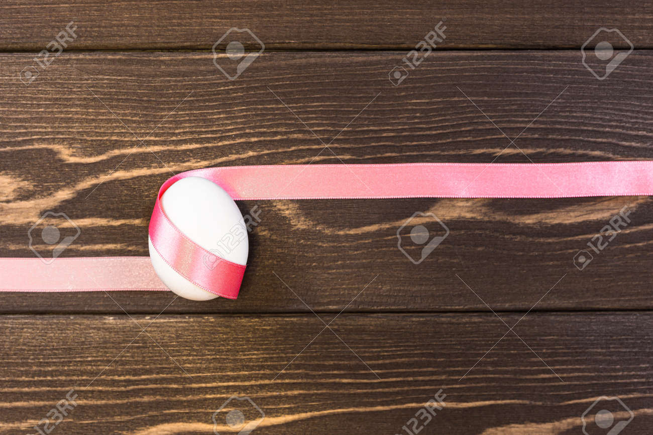 Easter egg is tied pink ribbon on the wooden background - 168607751