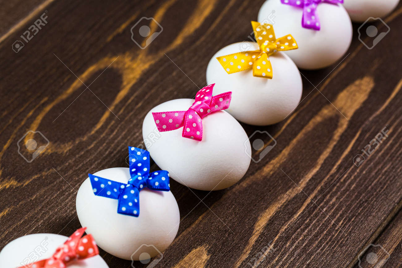 Line of easter eggs with colorful bows are on the wooden background. - 168607779