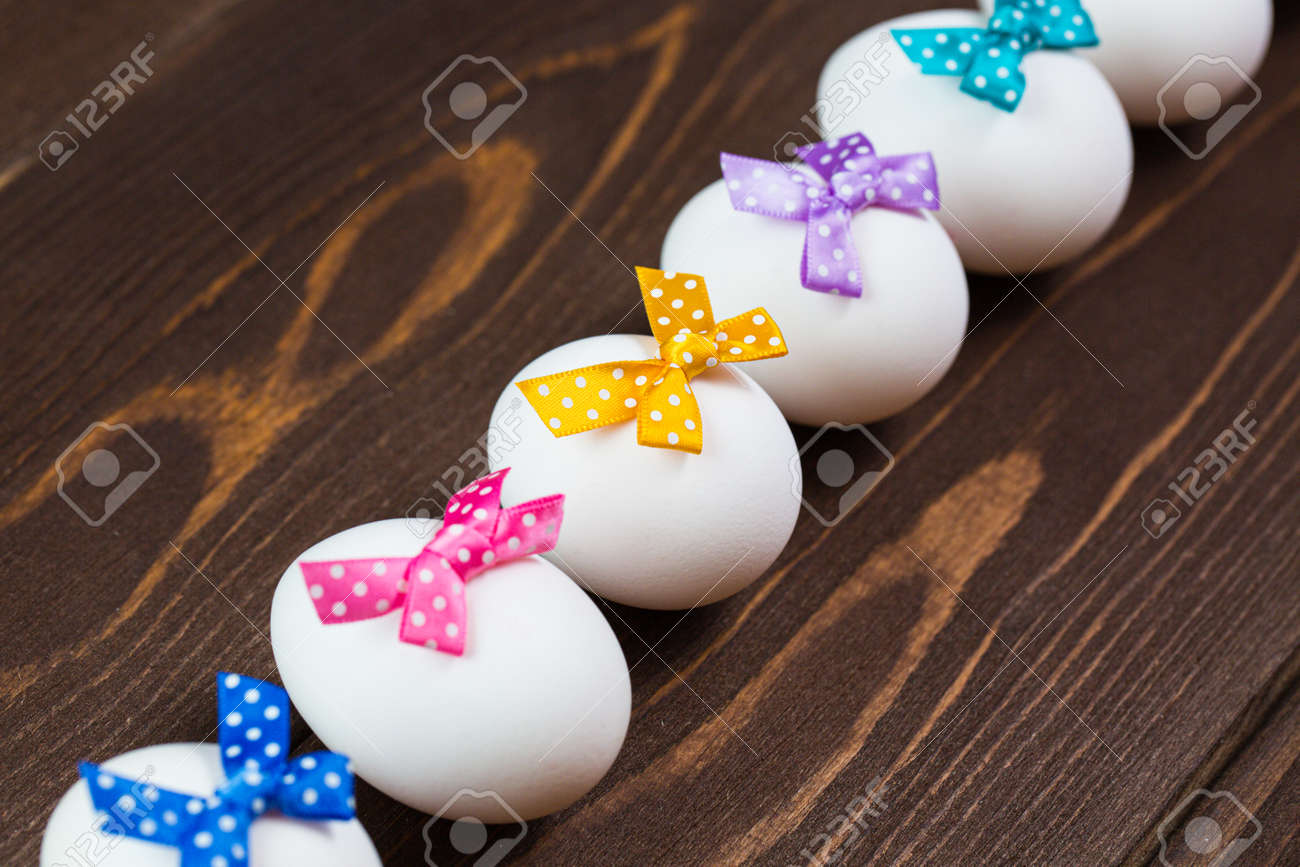 Line of easter eggs with colorful bows are on the wooden background. - 168607752
