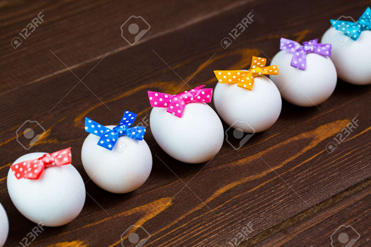 Line of easter eggs with colorful bows are on the wooden background. - 168607753