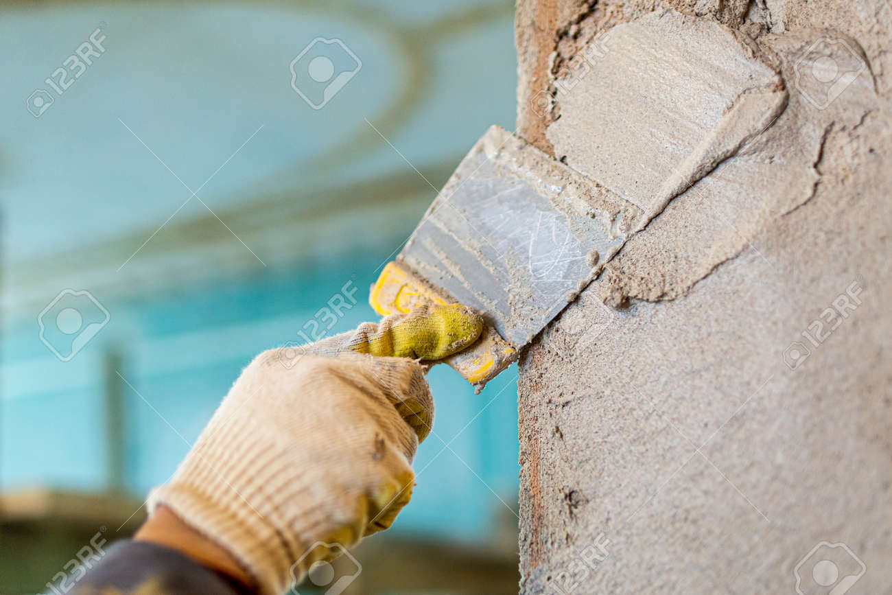 Worker is cementing by the putty knife the wall in room that is under construction, remodeling, renovation, extension, restoration and reconstruction. Focus effect on the workers hand. - 168608374