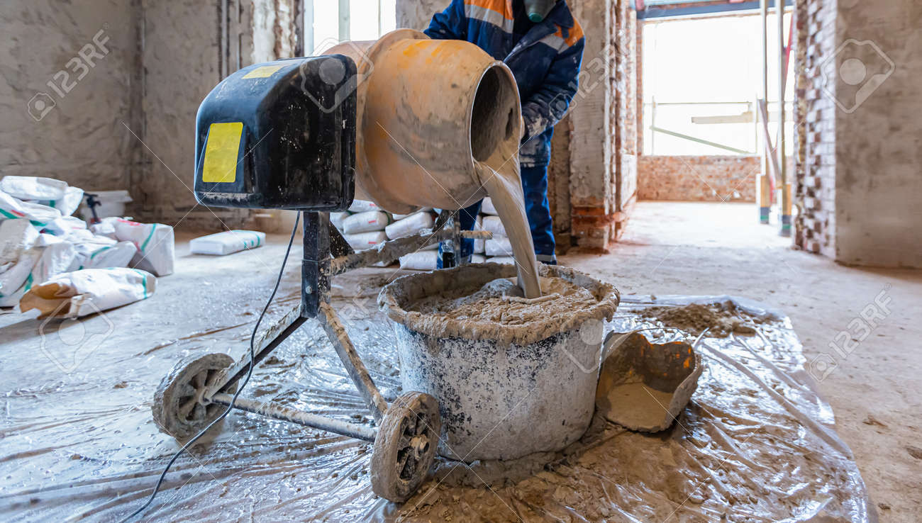 Worker is using the electric concrete mixer in an apartment is under construction, remodeling, renovation, extension, restoration and reconstruction. - 170616684