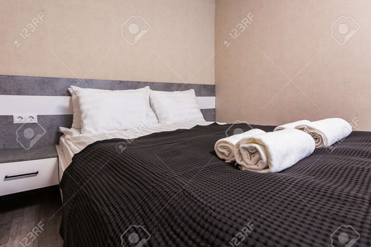 Two white towels and two striped pillows are on the bed in hotel room. Stack of towels on a hotel bed. - 170616691