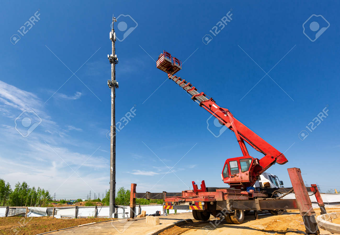 An aerial work platform, also known as an aerial device, elevating work platform, cherry picker, bucket truck, mobile elevating work platform maintenances the telecommunication tower. - 170616780