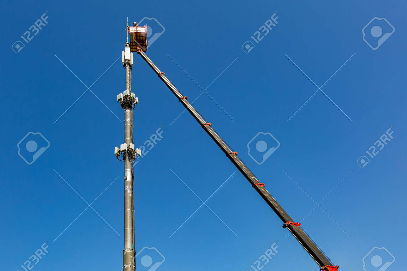 Engineer is working on the telecommunication tower - cellular phone repeater mast - from An aerial work platform, also known as an aerial device, elevating work platform, cherry picker, bucket truck, mobile elevating work platform - 170616799