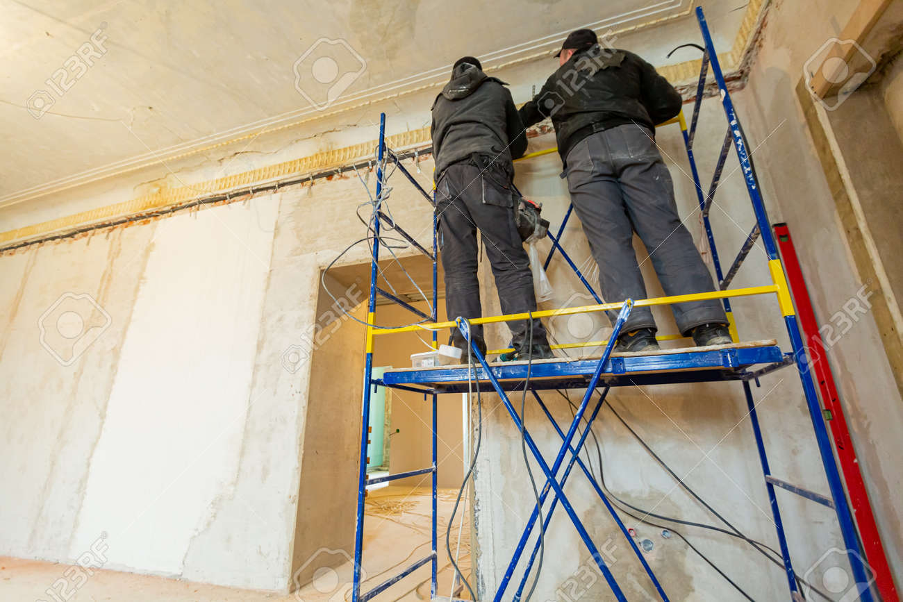 Two workers is installing the electrical wires on the wall that is the part of internal wiring in apartment that is under construction, remodeling, renovation, extension, restoration and reconstruction - 169988328