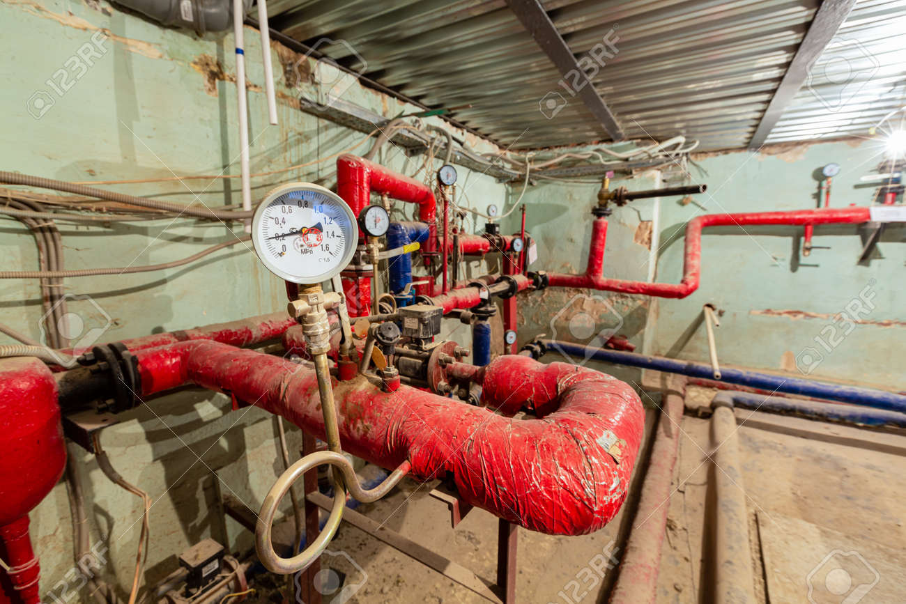 Manometer of center plumbing system and valves, stainless ball valves, detectors of water pressure and plastic and steel pipes of central heating system and water pipes with red thermal insulation in the boiler room. Concept of old independent private furnace room or heat boiler station - 170083211