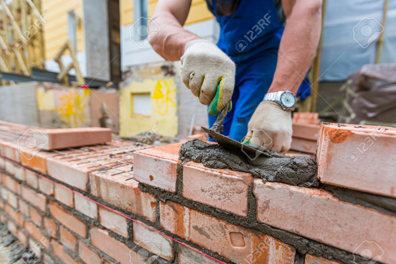 Bricklayer is laying brickwork on exterior wall with putty knife in construction site. - 170114460