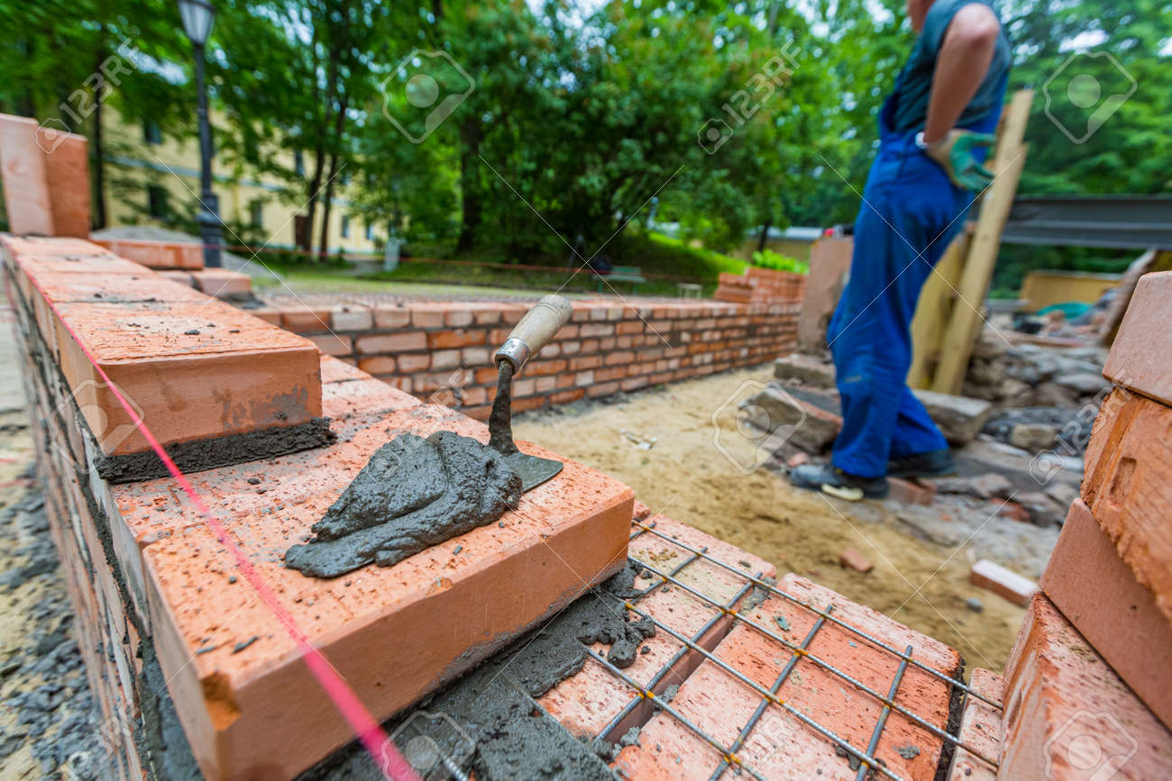 Putty knife with cement and bricklayer is near brickwork on exterior wall on construction site. - 170273851