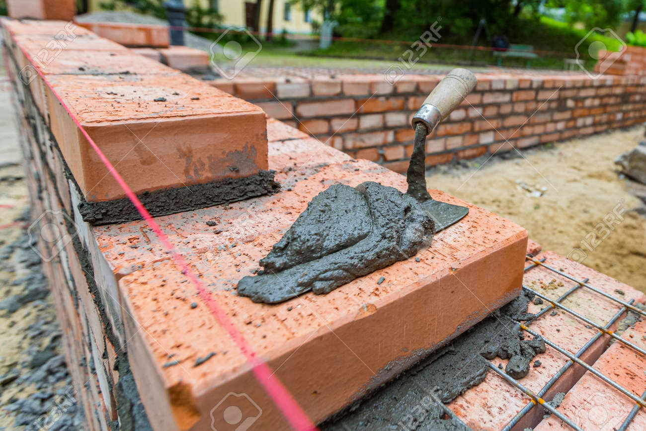 Putty knife with cement on the brickwork in construction site. - 170273359