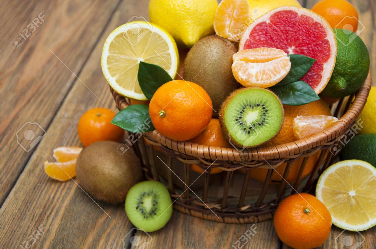 Fresh juicy citrus fruits in a basket on a wooden background - 52315233