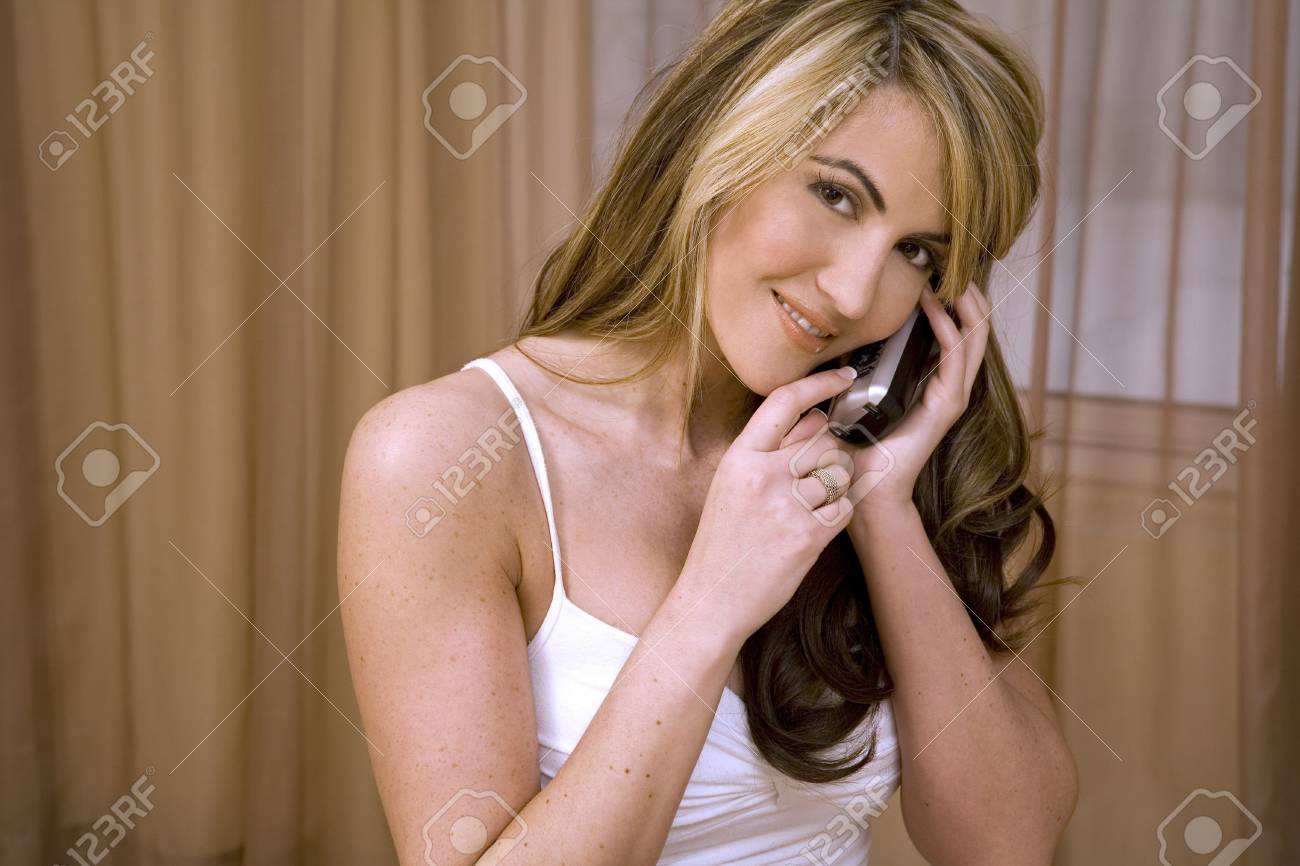 beautiful woman wearing white underwear and posing in her bed talking on the phone Stock Photo - 785523