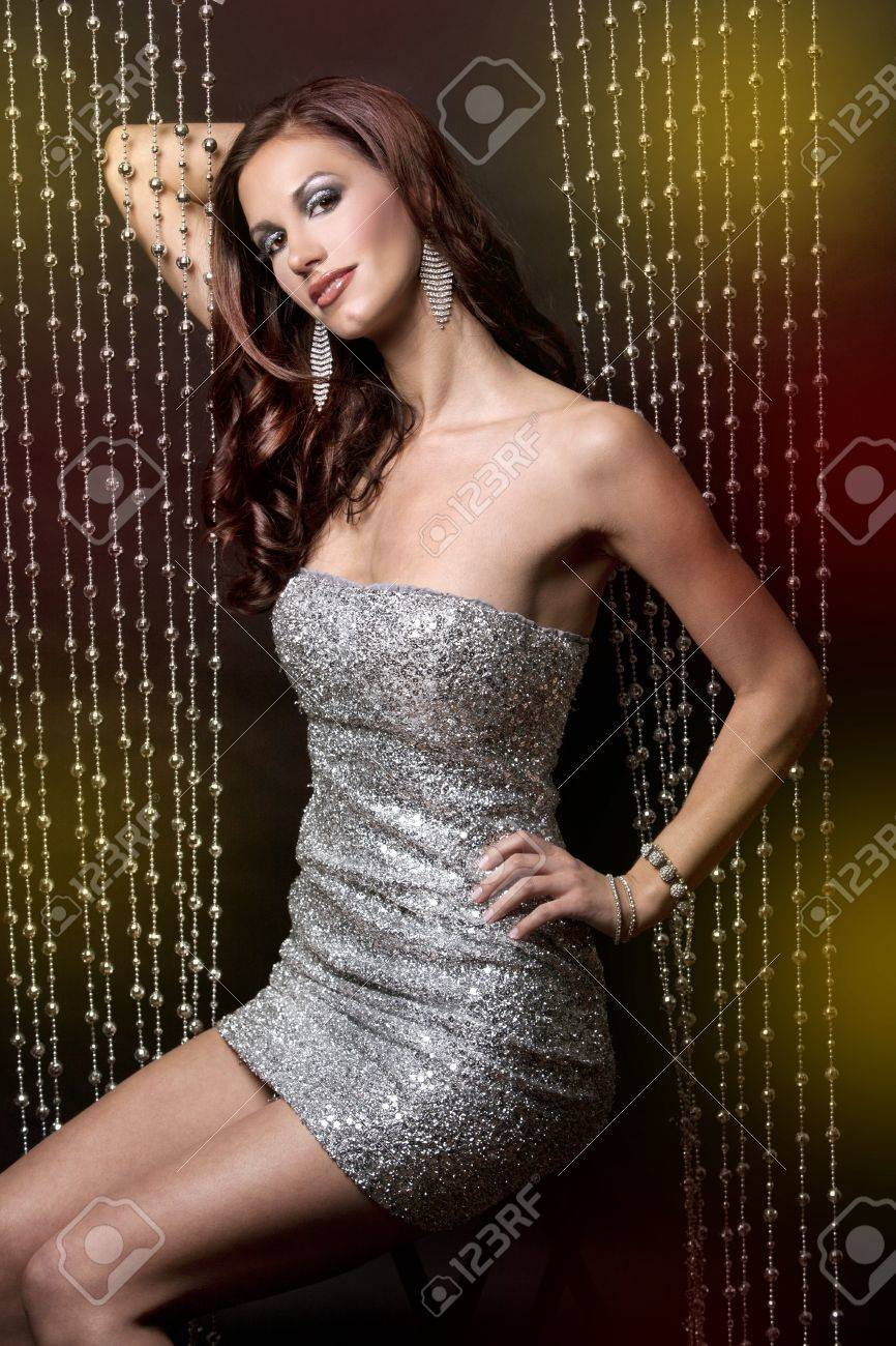 pretty brunette wearing silver party dress on black background Stock Photo - 12478407