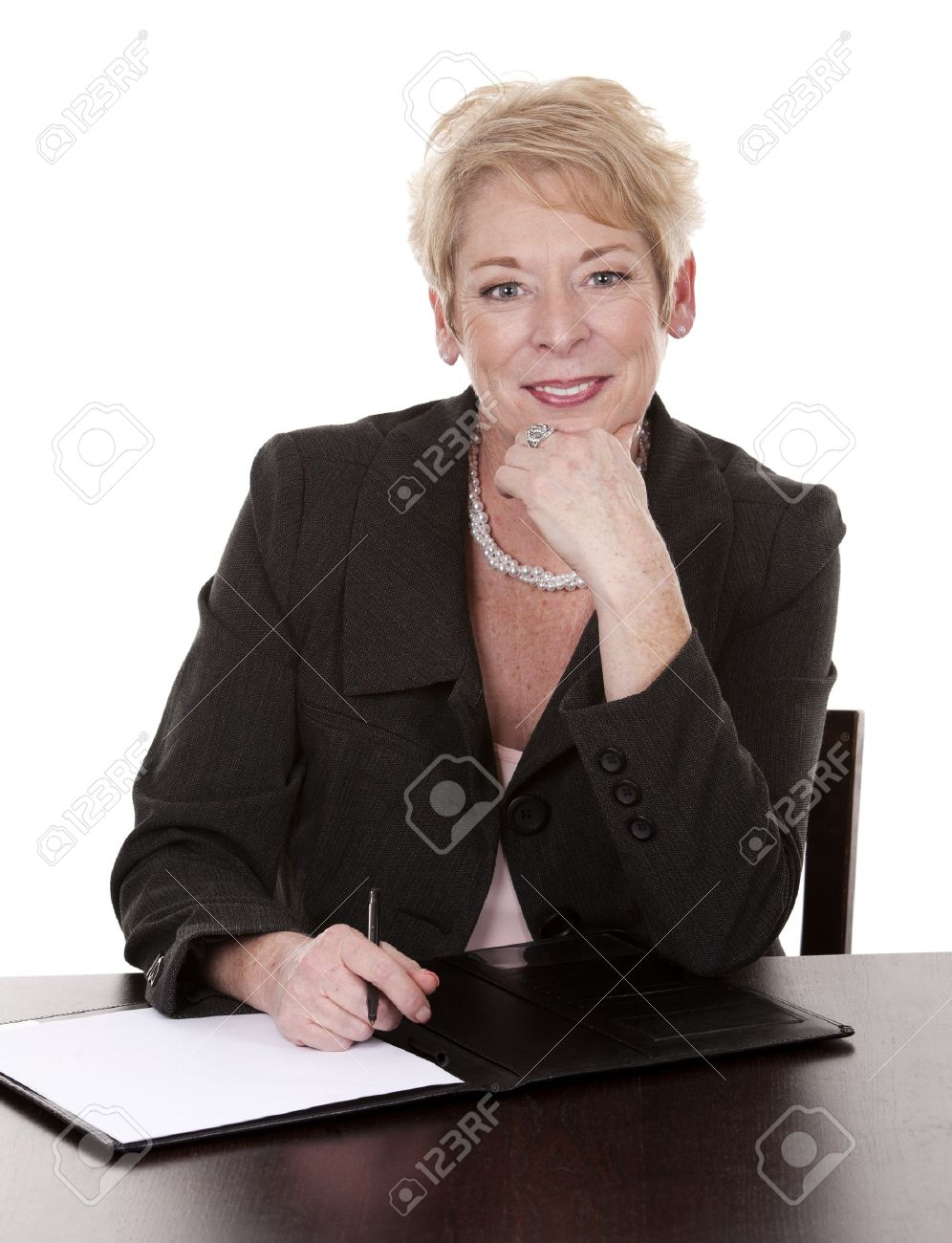 mature woman sitting behind desk and writing notes down stock photo