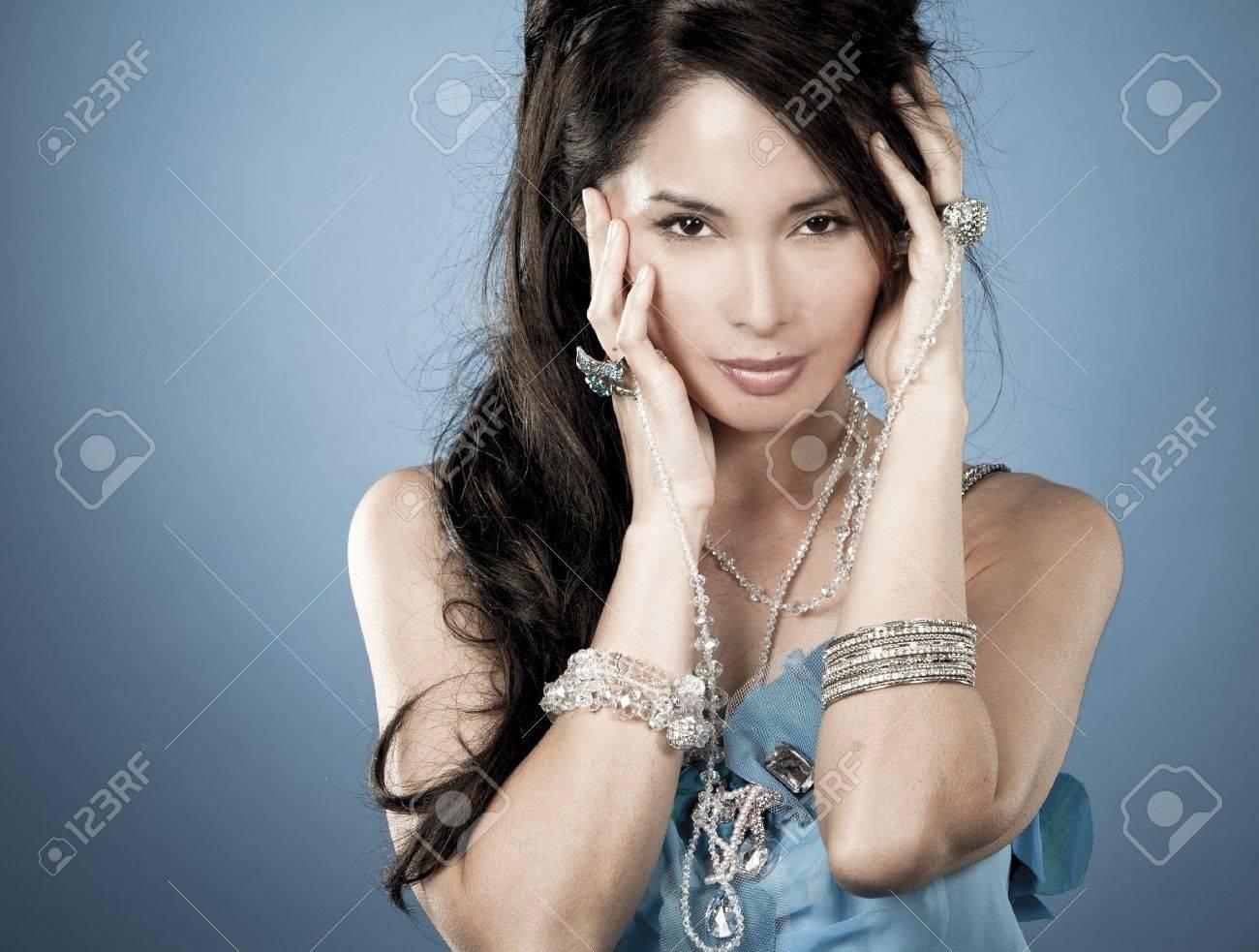 beautiful asian brunette wearing jewellery and fashin dress on blue background - 16757025