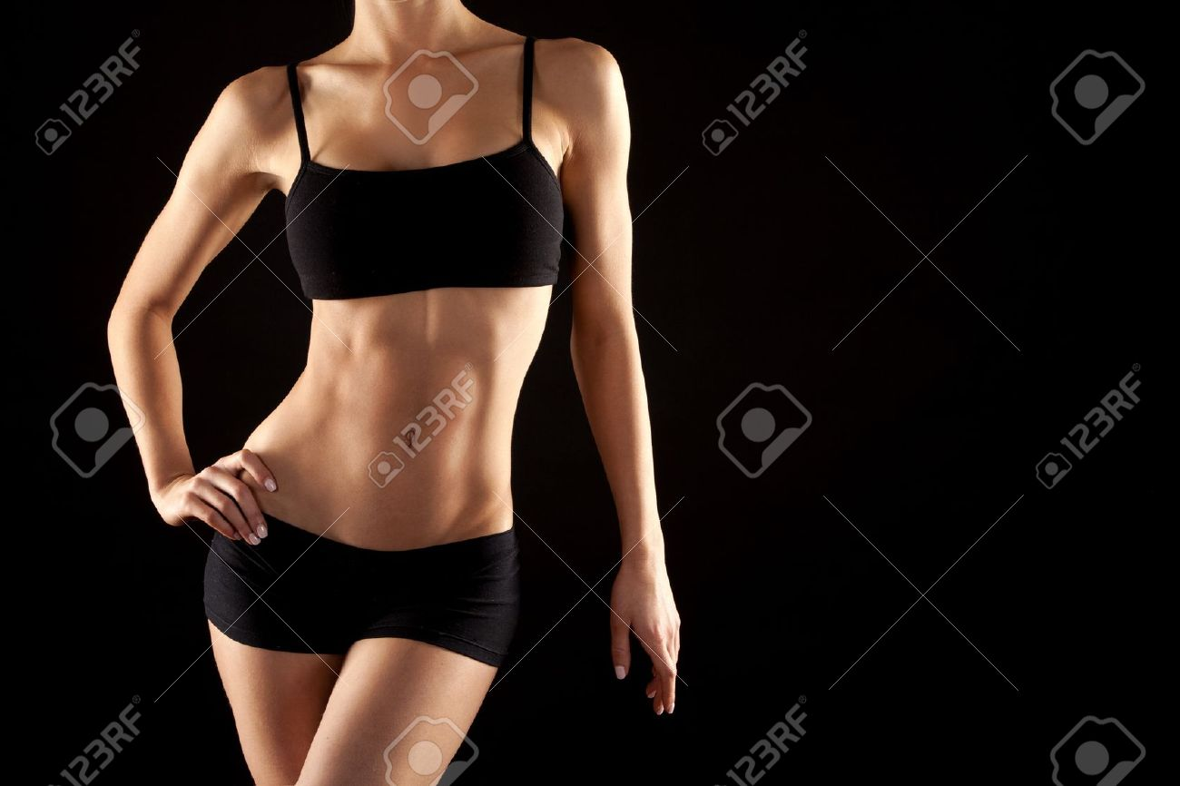 female fitness model posing on black background - 19062294