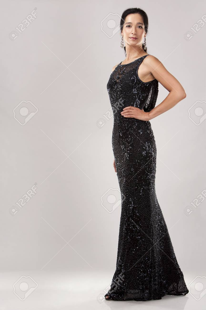 beautiful woman in her 40s wearing black evening dress on light background Stock Photo - 20603733
