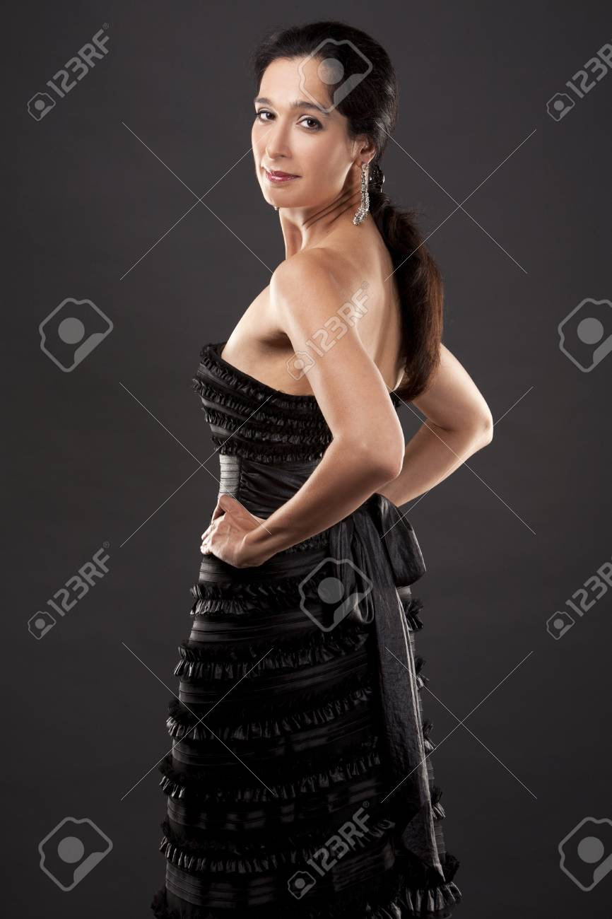 beautiful woman in her 40s wearing black evening dress on light background Stock Photo - 21172556