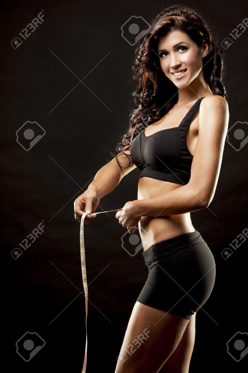 fitness model brunette measuring waist on black background - 22706450