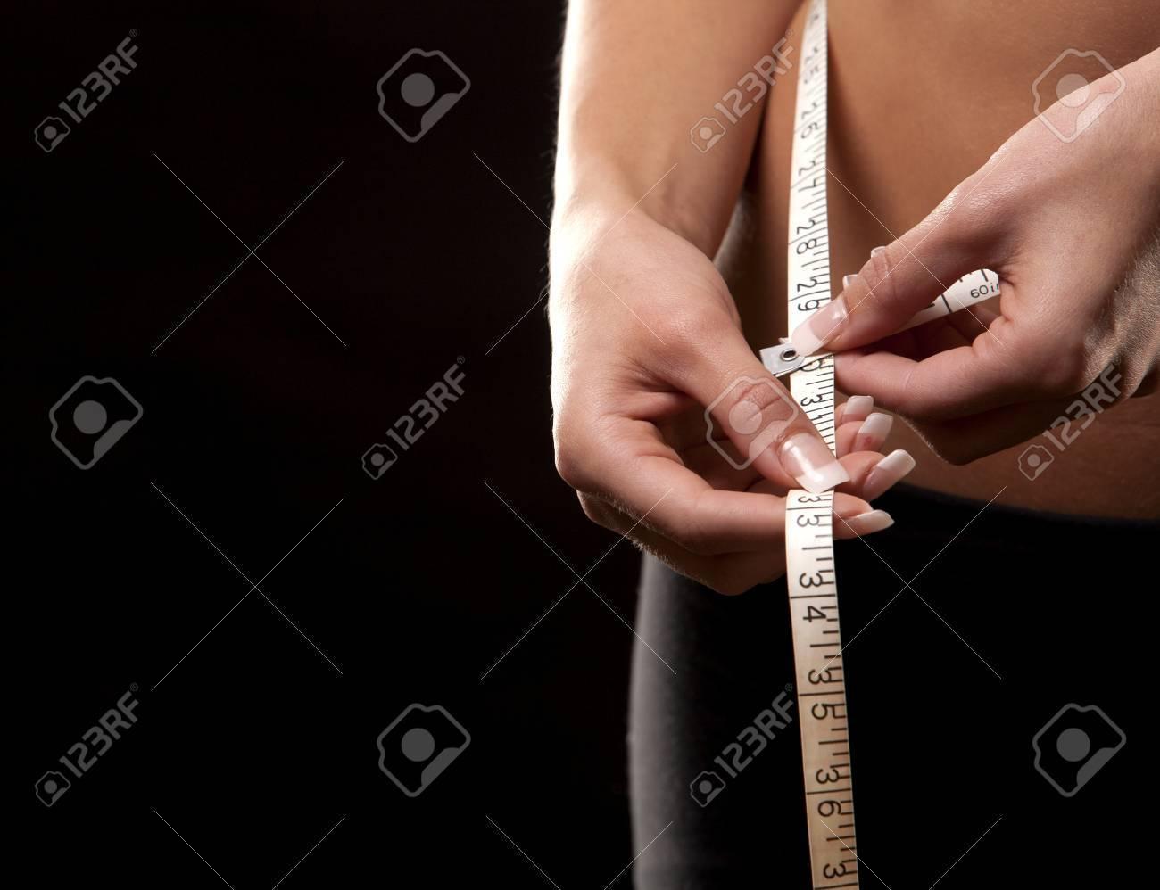 fitness model is measuring her waist on black background Standard-Bild - 22880252