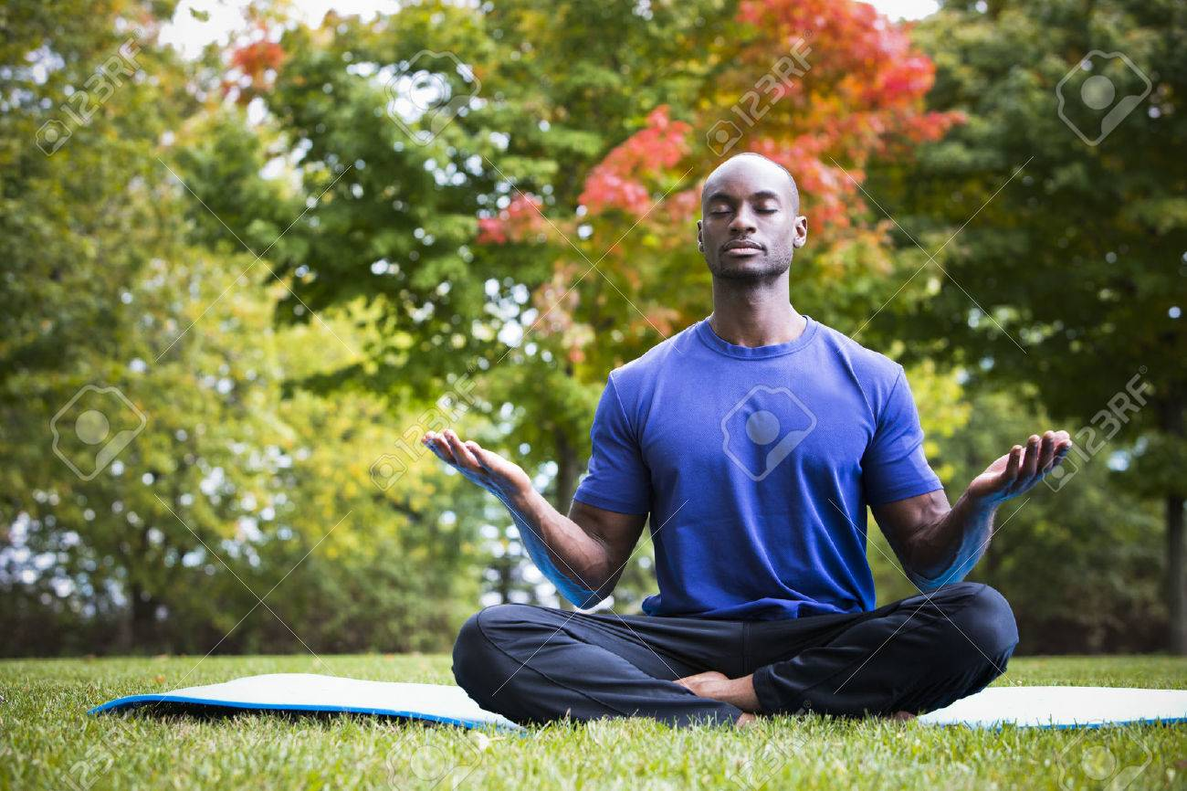 young black man wearing athletic wear sitting in the park exercising yoga Standard-Bild - 64666561