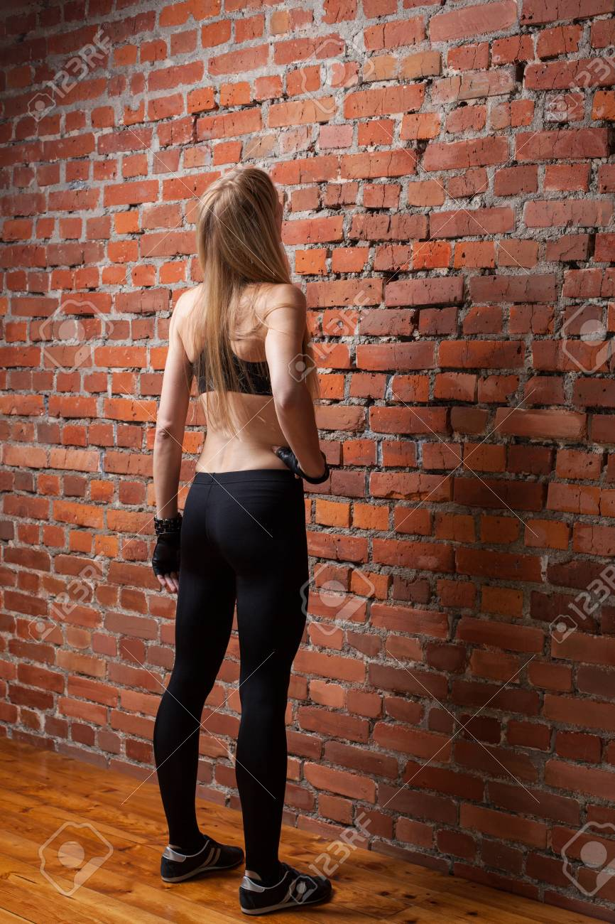 Beautiful Adult Fitness Lady In Black Top And Leggings Standing In Front Of The Brick Wall