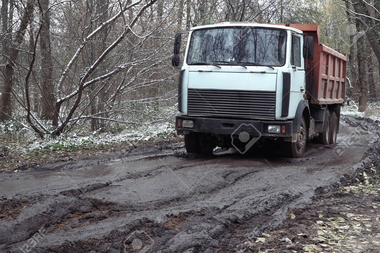 truck going on the rutted road through the autumn forest stock photo