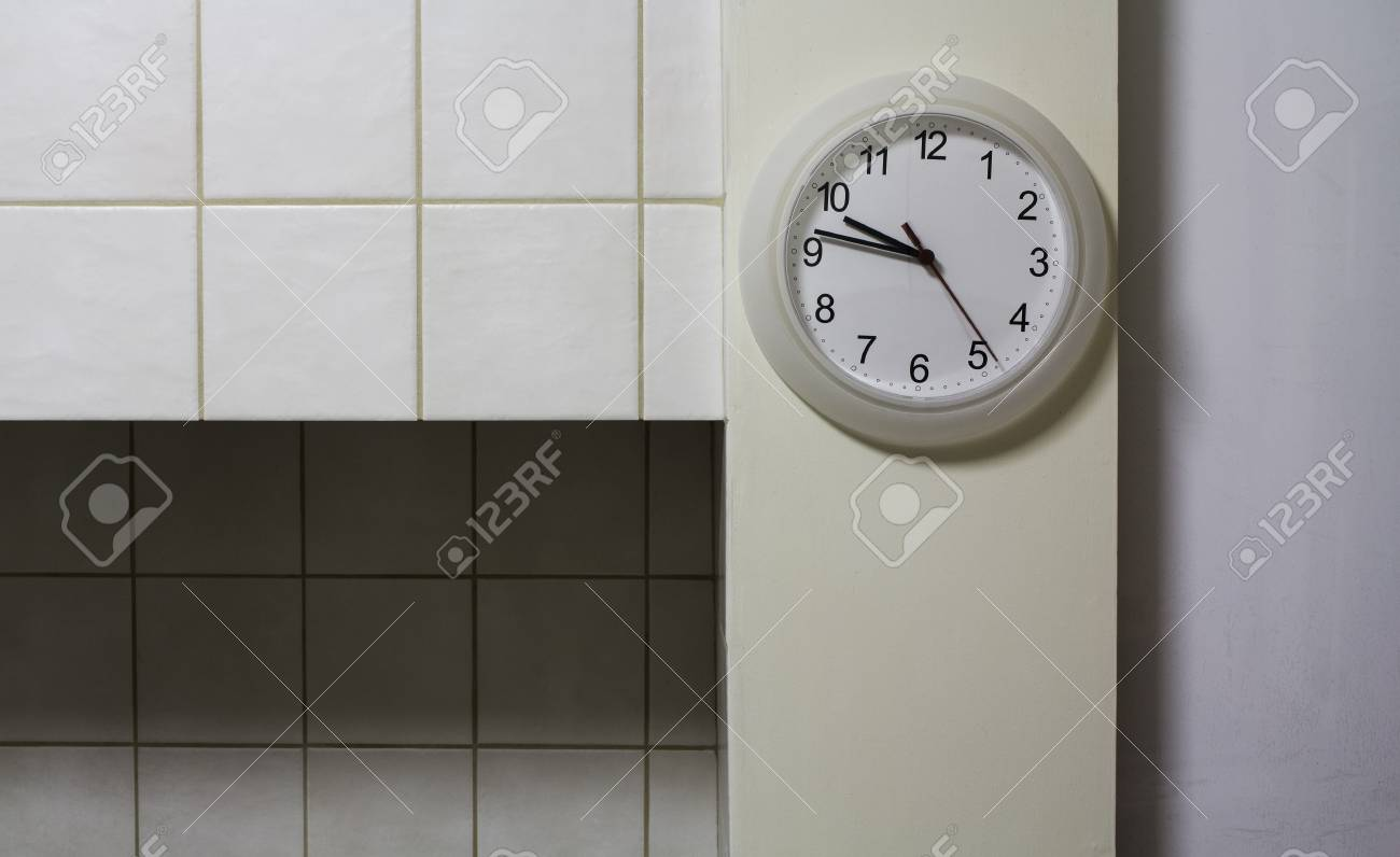 Orologio da cucina sul muro di piastrelle foto royalty free
