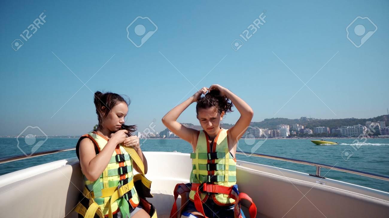 Stock Photo - Two beautiful teen girls dancing on a yacht cruising fast on  open sea horizon