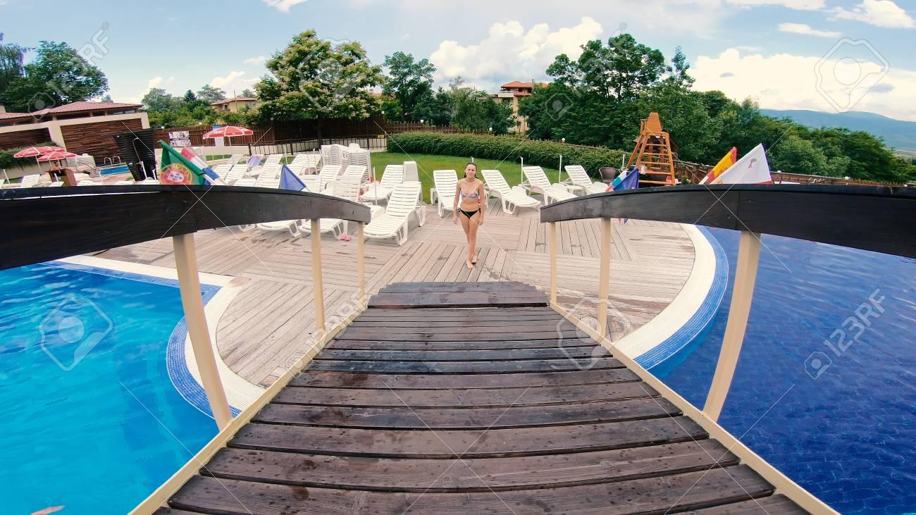 Fit teen female walks over wooden bridge at swimming pool, steadicam..