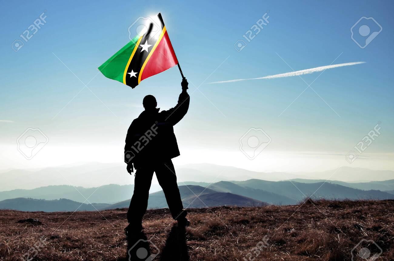 Successful silhouette man winner waving Saint Kitts and Nevis flag on top of the mountain peak - 120322831