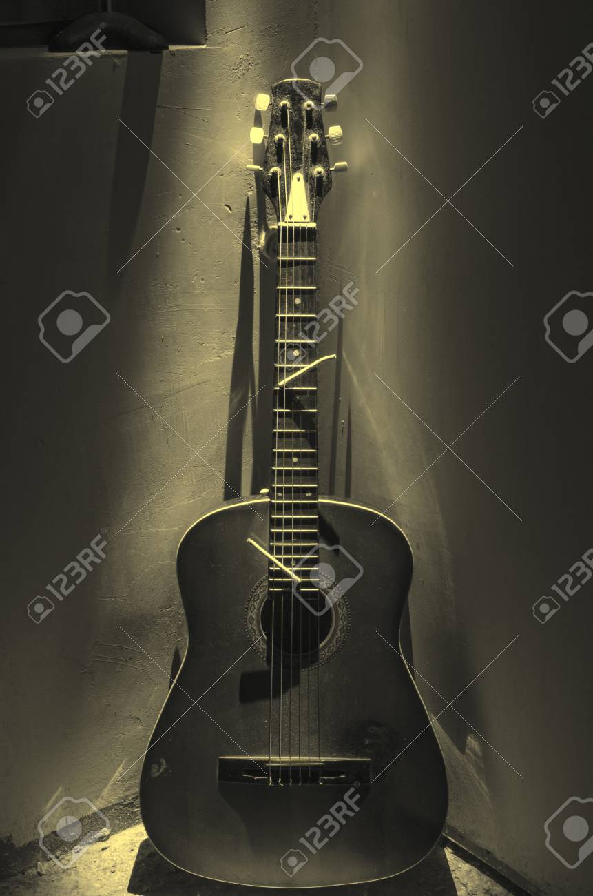 Acoustic guitar leaning on rusty wall in dark room with lights