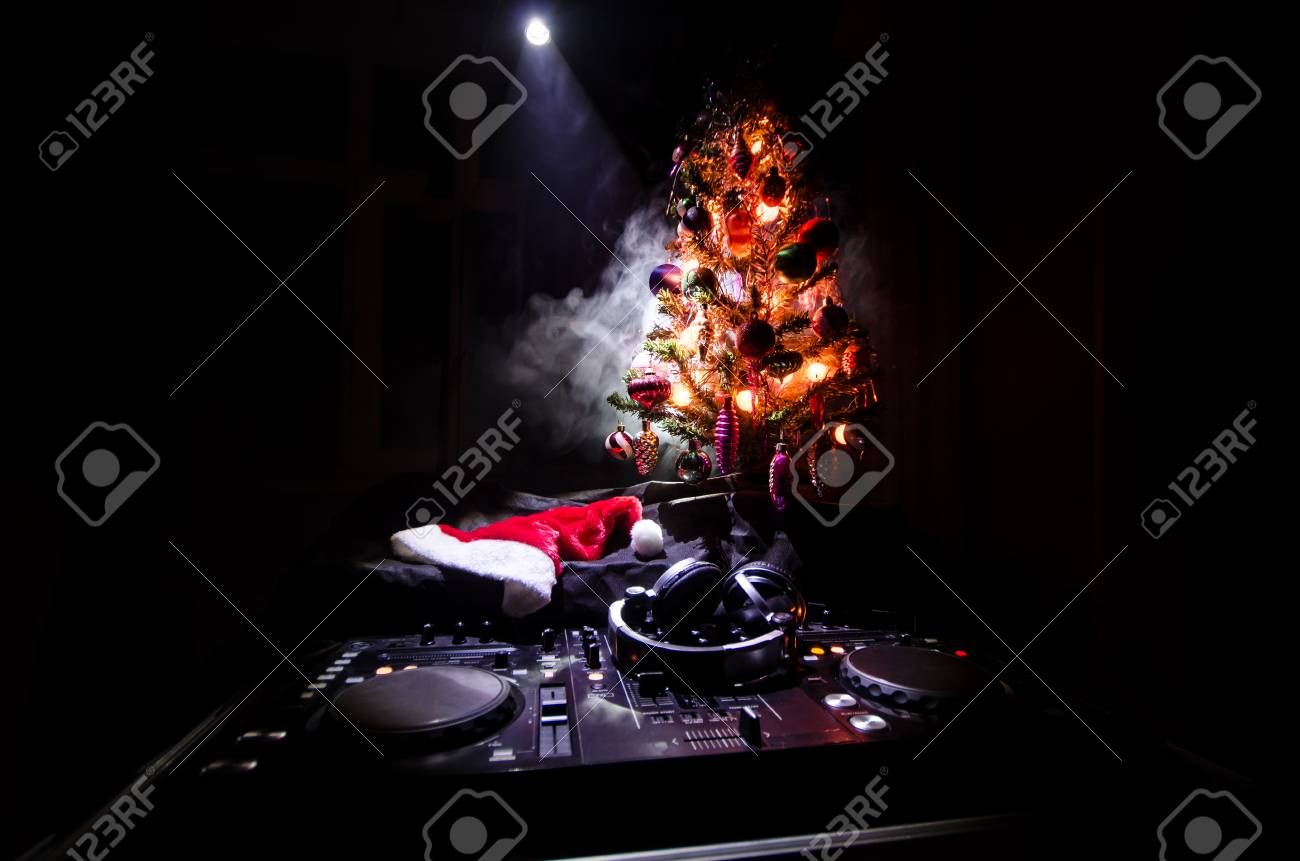 Dark Christmas.Dj Mixer With Headphones On Dark Nightclub Background With Christmas