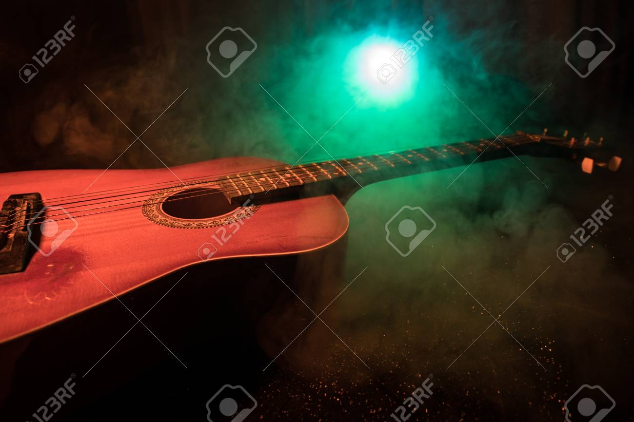 Music Concept Acoustic Guitar On A Dark Background Under Beam