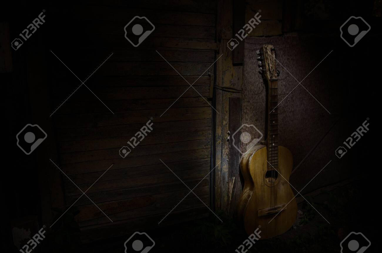 An wooden acoustic guitar is against a grunge textured wall. The room is dark with a spotlight for your copyspace. old broken guitar - 128832571