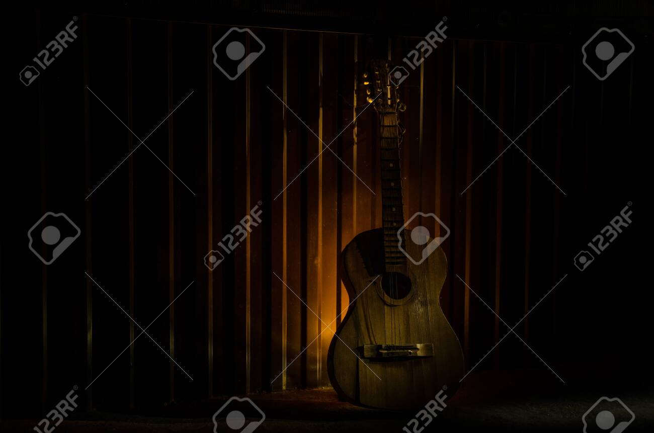 An wooden acoustic guitar is against a grunge textured wall. The room is dark with a spotlight for your copyspace. old broken guitar - 128832592