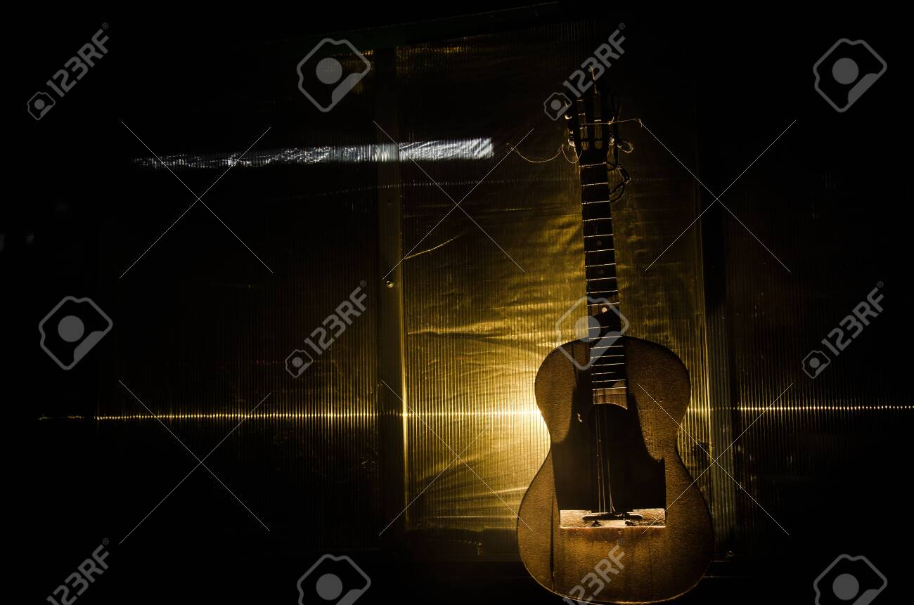 An wooden acoustic guitar is against a grunge textured wall. The room is dark with a spotlight for your copyspace. old broken guitar - 128917759