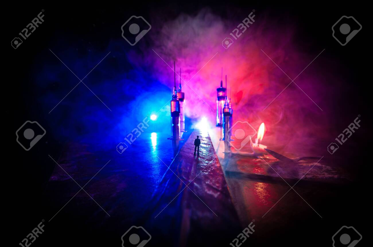 Narcotic drug problem concept. Silhouette of a man standing in the middle of the road on a misty night with giant Drug syringe and narcotic attributes. Creative artwork decoration - 142571851