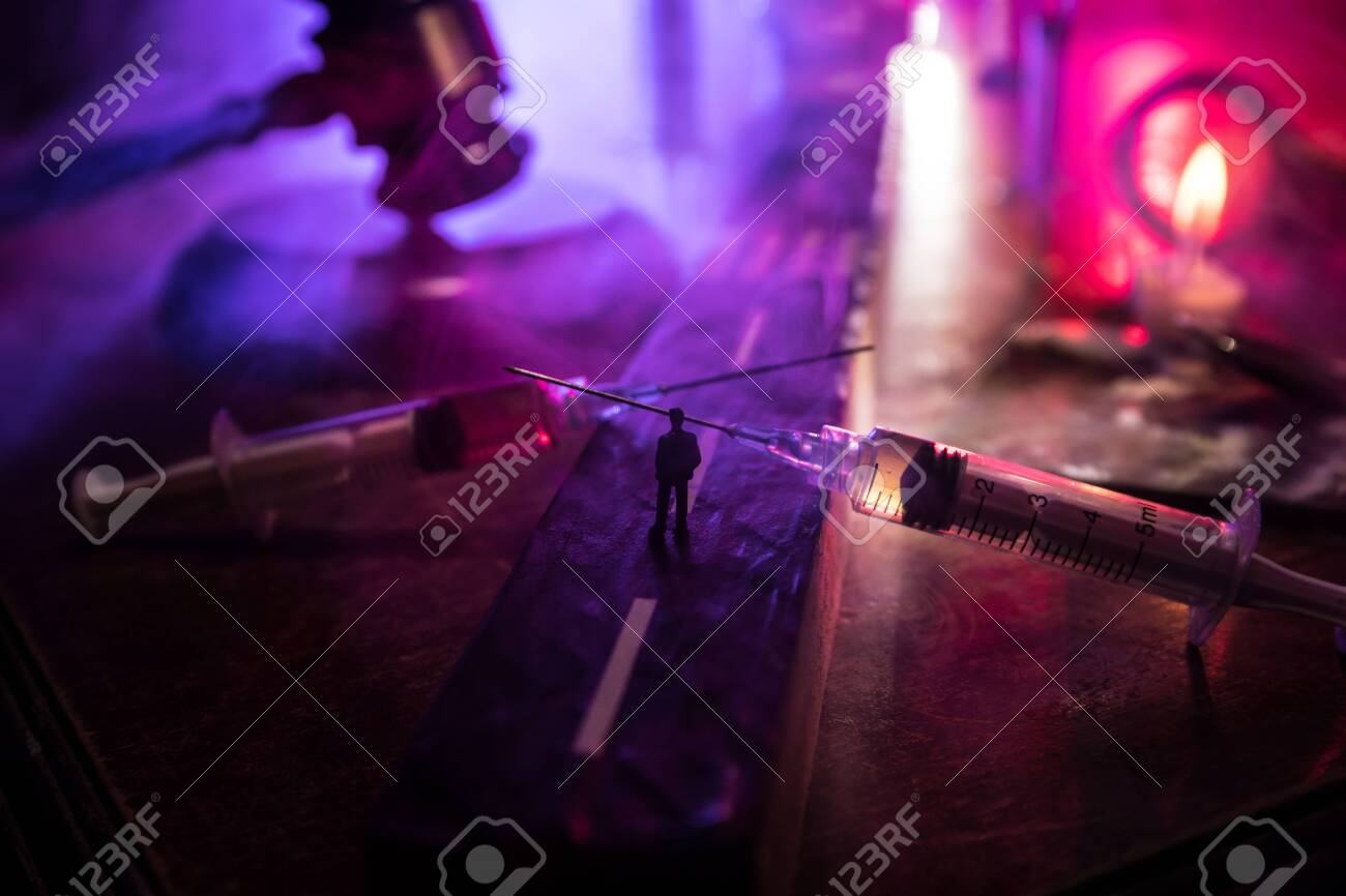 Narcotic drug problem concept. Silhouette of a man standing in the middle of the road on a misty night with giant Drug syringe and narcotic attributes. Creative artwork decoration - 144612533
