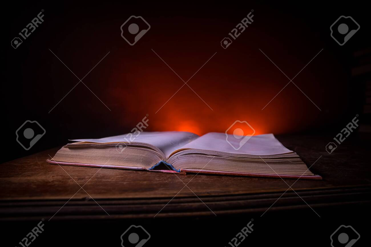A stack of old books. Vintage book on wooden table. Magic lightning around a glowing book in the room of darkness. Selective focus - 156061803